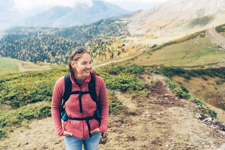 A woman with a backpack on a fine autumn day high in the mountains. Place for text.