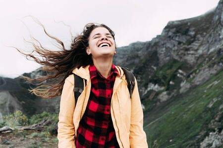 A girl with long curly hair windblowing laughing and enjoying freedom at the top of the mountain
