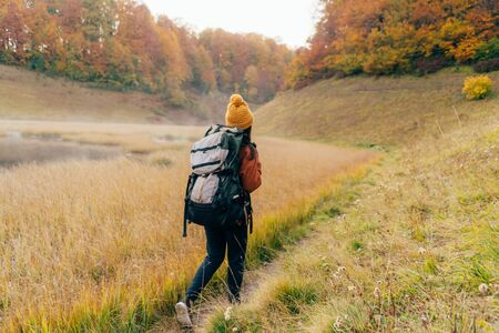 A woman with a heavy backpack is walking along the path to the forest. Autumn concept. Healthy lifestyle. Expedition to the mountains in the fall season.