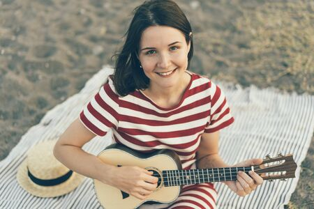 A cute white young brunette gypsy in a shabby casual dress on the sand at the beach plays ukulele guitar and smiles. Cheerful youth content. Inspirational and festive mood.