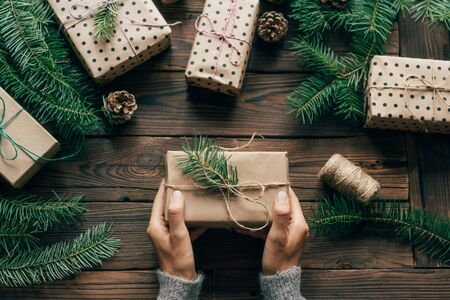 Top view of a wooden surface on which lie gift boxes and fir branches. Female hands hold one gift in simple natural wrapping paper. Cute Christmas flat lay. Festive concept. Banco de Imagens