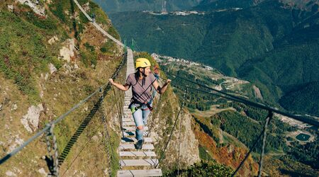 Young happy woman tourist is walking on a rope bridge hanging at the peak of the mountain. Adventurer and lover of extreme and adrenaline.