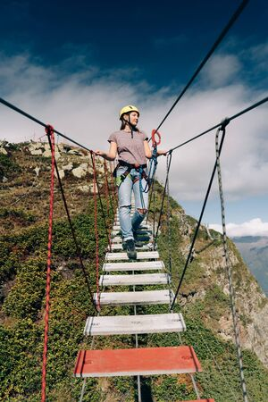 Young happy woman climber is walking on a rope bridge hanging in the mountains over the precipice. Adventurer and lover of extreme and adrenaline. Extreme vacation concept. Banco de Imagens
