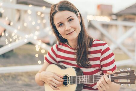 A young beautiful white authentic female gypsy hipster looks at the camera and plays on an acoustic ukulele on the beach against the background of bokeh of garland lights.