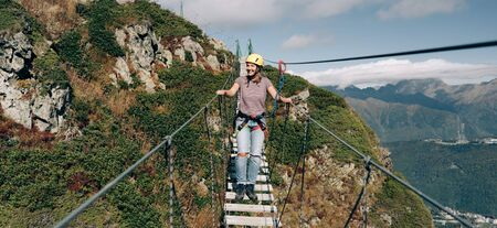 Extreme female walks on a suspension bridge in the mountains over a precipice.