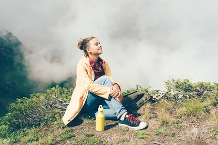 Young white hipster woman high in the mountains against the background of clouds resting and enjoying the natural beauty. Copy space for text. Banco de Imagens