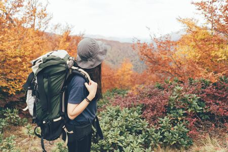 Girl on an expedition trip with a heavy backpack and bucket hat in a forest in the mountains on an autumn warm day.