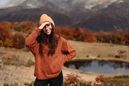 Cute young woman in a sweater and hat in the mountains by the lake in the autumn season.