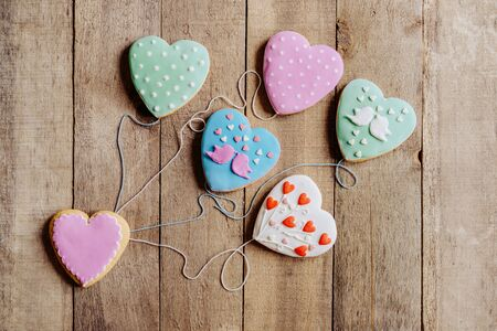 On a wooden background are five glazed gingerbreads in the shape of hearts on threads like balloons. Banco de Imagens