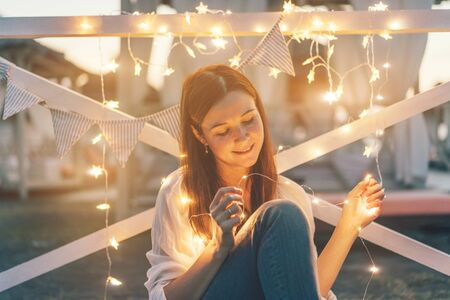 A young beautiful white female hipster sits amid a garland and holds it in her hands. Magic chamber holiday content. Copy space for text. The festive miracle Christmas mood.