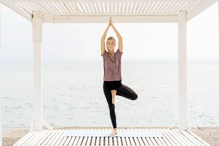 A woman in sportswear on the seashore stands in the yoga pose of a tree and holds balance on one leg. Banco de Imagens