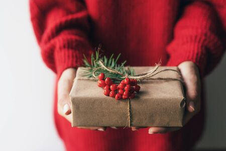 Elegant female hands holding a gift box decorated with red berries. Merry Christmas.