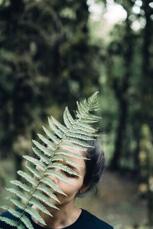 Mysterious art portrait of a woman in a forest with a fern branch covering her face.