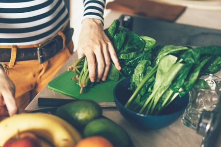 The process of preparing food for cooking dinner. Sliced ​​spinach. Female hands. Kitchen care. Banco de Imagens