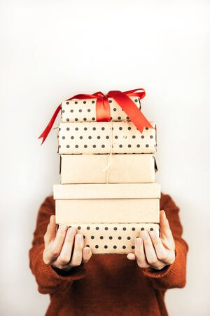 Closeup stack of boxes in female hands. A face of person is not visible. Vertical image