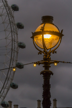Lantern and London Eye on the street at evening in London Stock Photo