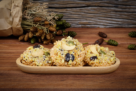 sesame cracker: Rice Cracker topped cereals placed on a wooden tray .