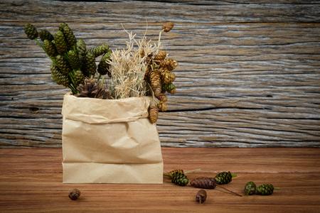 flores secas: flores secas en una bolsa de papel, se puso en el suelo de madera.