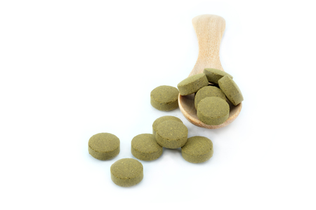 nutritional therapy: Herbal medicines in the spoon on white background.