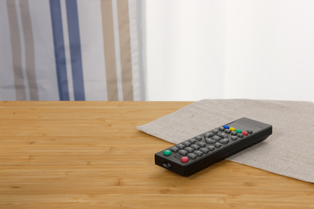 The remote control is placed on a wooden table with the morning sun. Warm moments and enjoy