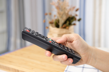 Remote control in hand, are pressing to watch TV in the morning.