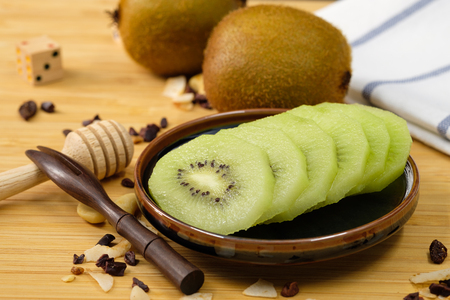 Kiwi slices were placed on a ceramic plate Stock Photo
