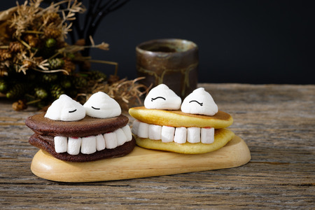 marshmellow: Halloween marshmallow and monster teeth smiling happily on a black plate Stock Photo
