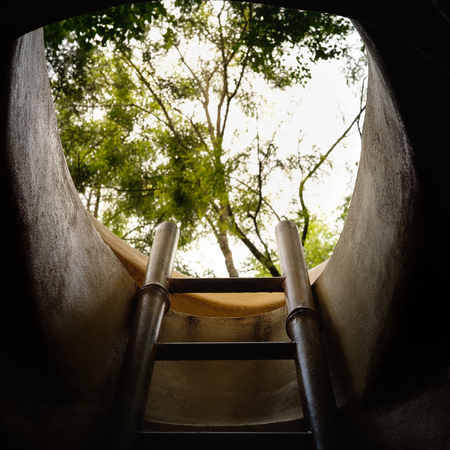 dark cave: The stairway to the exit of a tunnel shined by sun light, Climb out of the dark cave. dark Stock Photo