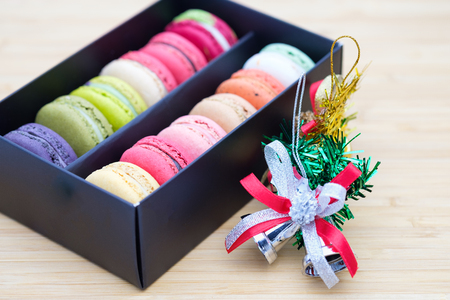 Sweet and colorful macaroons cookies in the black box on wooden background with blank space,selective focus, Dessert. Stock Photo