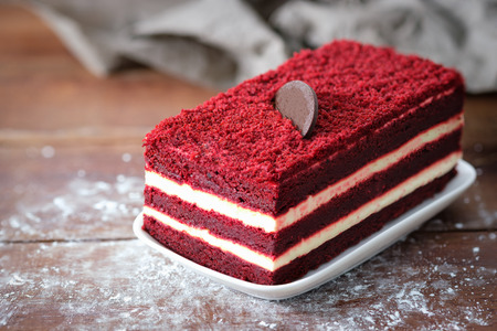 Red velvet cake and white cream on wooden table, close up, space to write.