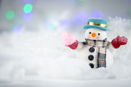 A snowman and mini heart pillow on bokeh background, with copy space for season greeting. Merry Christmas or Happy New Year, AF point selection.