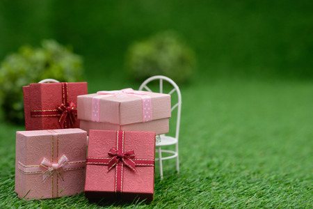 Gift box on white field chair in green garden, with copy space to write.
