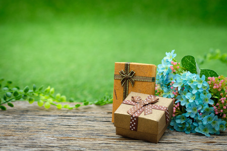 Gift box with as a present for Christmas, new year, valentine day or anniversary on decay wood in green garden background, top view, space for write.