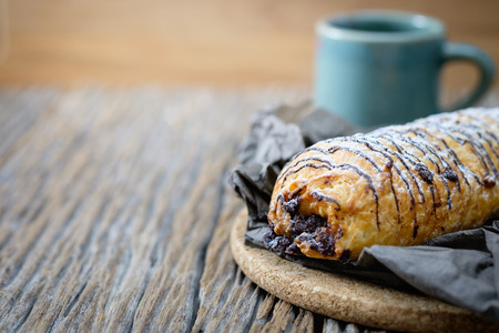 Homemade Chocolate Croissant Pastry with Powdered Sugar on wooden background.