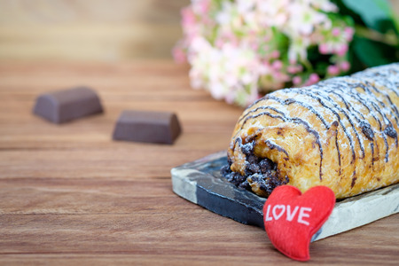 Homemade Chocolate Croissant Pastry with Powdered Sugar and shape on wooden background. Stock Photo