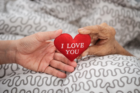 Hands of an elderly woman holding a red heart. Love in family concept.
