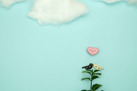 Wooden bird and a heart-shaped  on blue background with copy space for write and valentine concept.