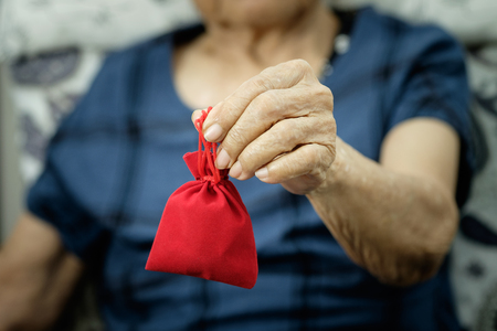 give money: Old hand give Money in Red bag for Chinese New Year. gift for Chinese New Year.