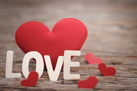 Forma roja del corazón de la almohada y palabra del amor en fondo de madera con el espacio para escribir. Concepto de San Valentín, tono Vintage, selección de punto AF.