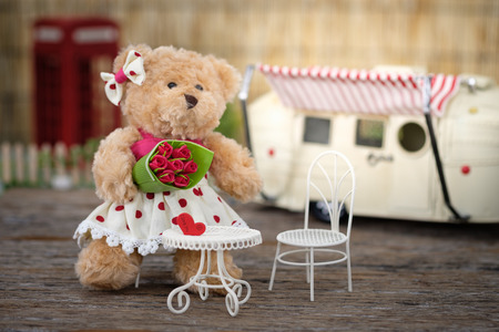 Teddy Bear holding a bouquet of roses in valentine concept with space for write, AF point selection and blur, Vintage tone picture. Stock Photo