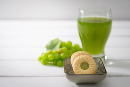 Biscuits put on a ceramic plate and green grapes placed close together on white wooden background, Selective focus.