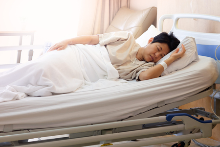 Asian woman sleeping In hospital bed, Morning sun shines into the room, AF point selection and blur. Stock Photo