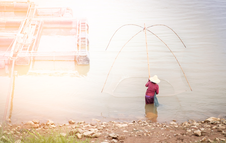 Women flattered fish on the river, Fishermen are flattering on canals near stew in sunset light.
