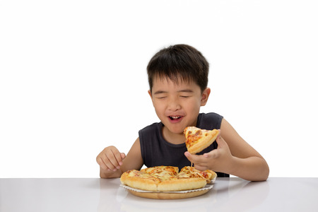 Asian boy is happy to eat pizza with a hot cheese melt stretched on a wooden pad.  Isolated over white. Banco de Imagens