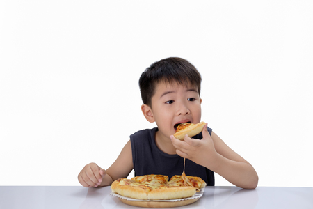 Asian boy  happy to eat pizza with a hot cheese is melting and stretching on a wooden pad.  Isolated on white background, choose focus point.