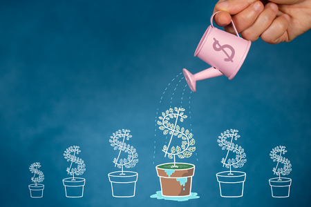 Hand with watering can pouring  to growing tree, Savings concept, Financial planning to grow.