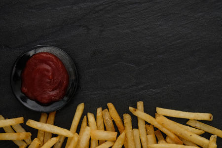 Fresh fried french fries with ketchup on black background. Choose focus point.