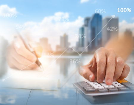 overlays: Hand is pressing calculator and write paper, There are overlays of buildings and cities, A concept of business, this image focuses on blurring to be used as the background.