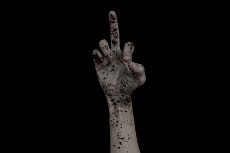 The hands of the zombies raise middle finger emerge from the grave dirty soil isolated on black background. Stock Photo