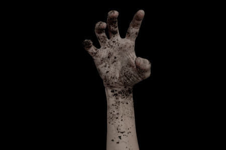 The hands of the zombies emerge from the grave dirty soil isolated on black background.